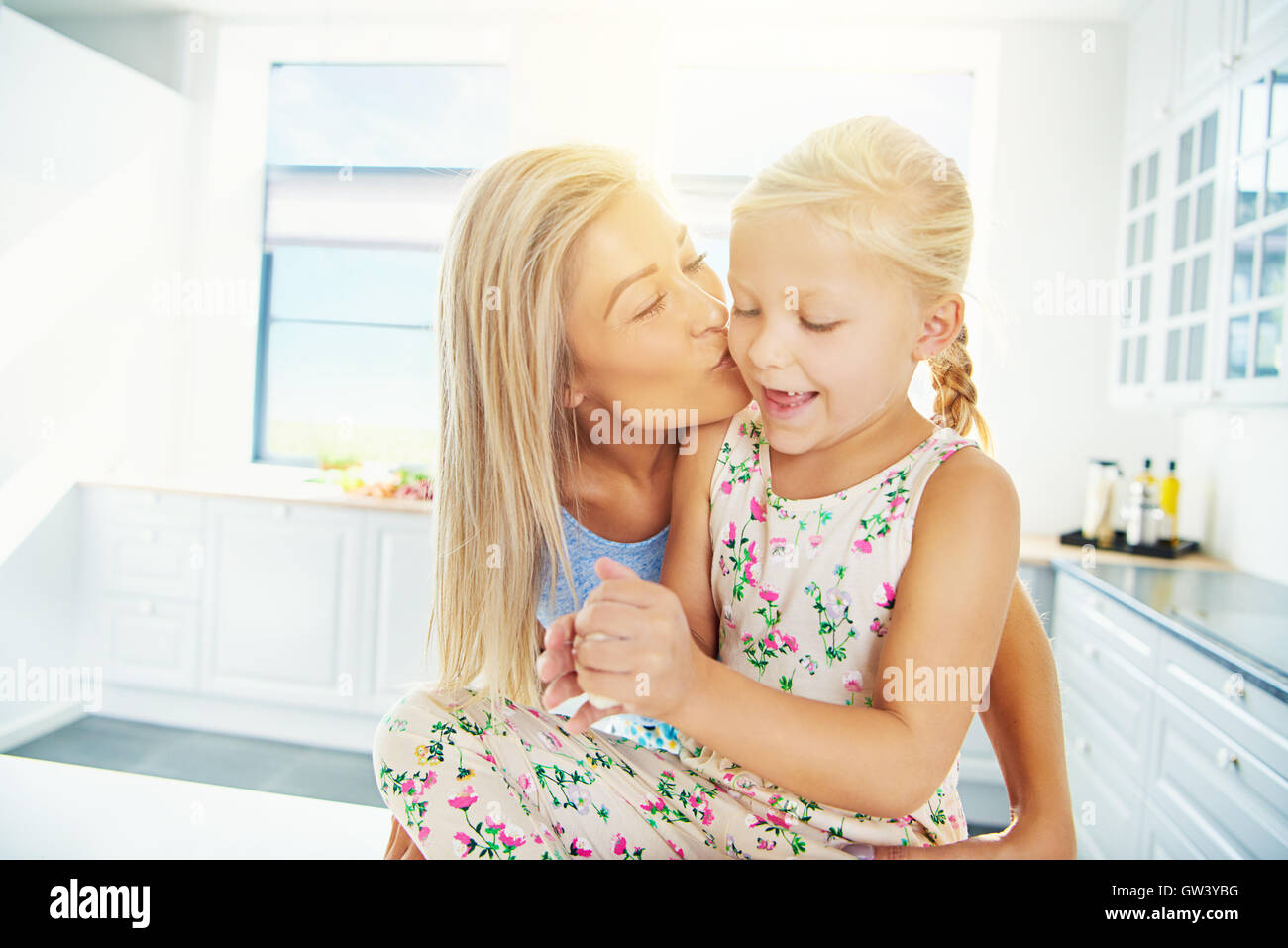 Beautiful young blond mother kissing daughter in ponytails and dress while she plays with bread dough - Stock Image
