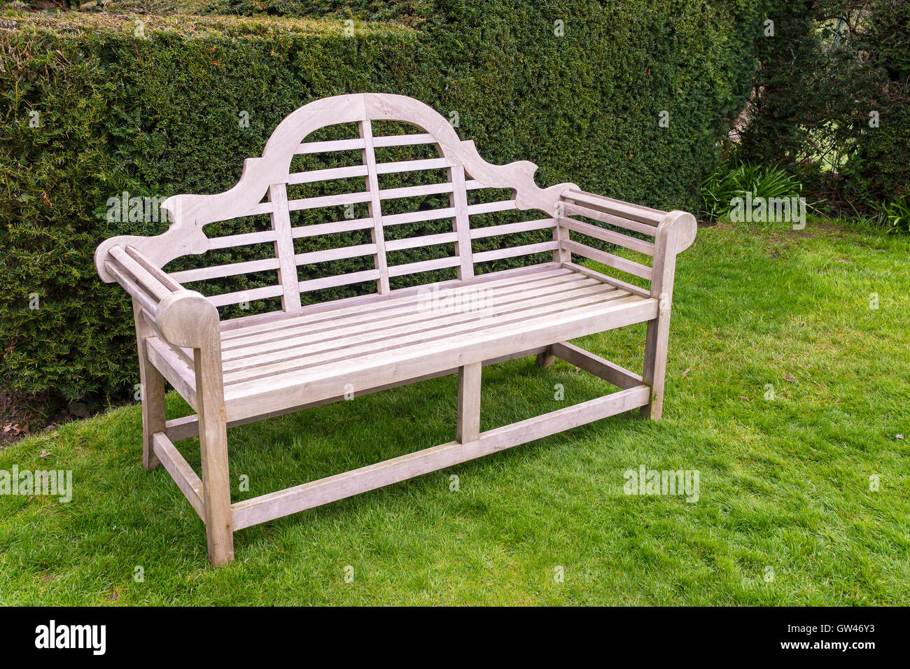 Wooden artisan bench on grassy lawn. Stock Photo