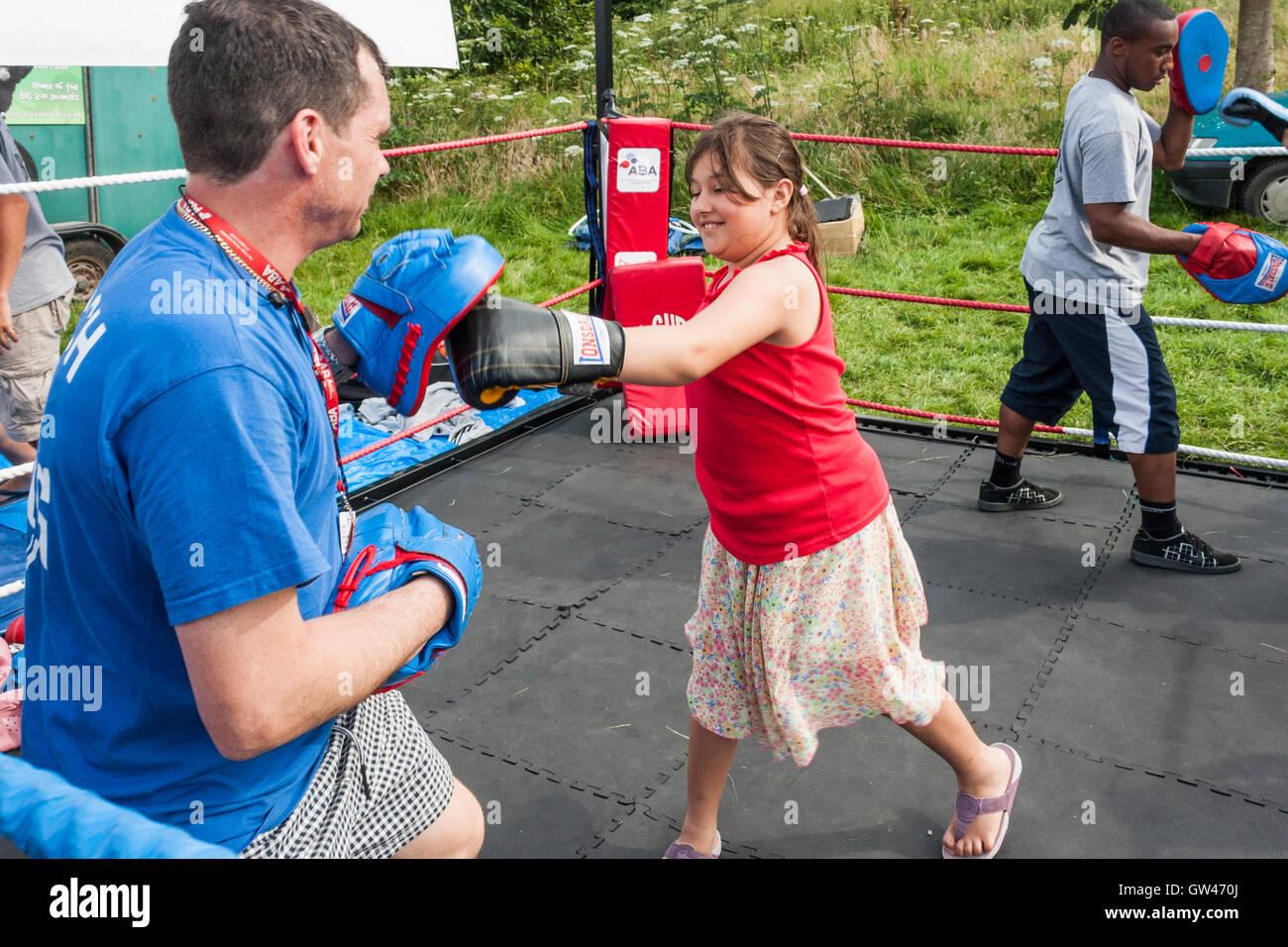 Boxing trainer teaching children to box - Stock Image