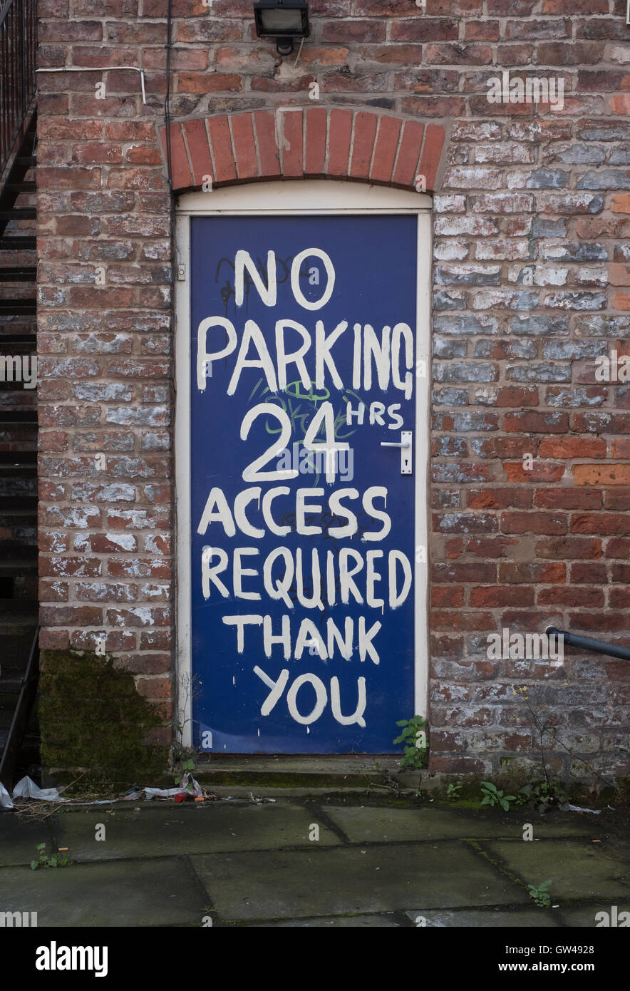 No parking restrictions daubed on wall at back of shop - Stock Image