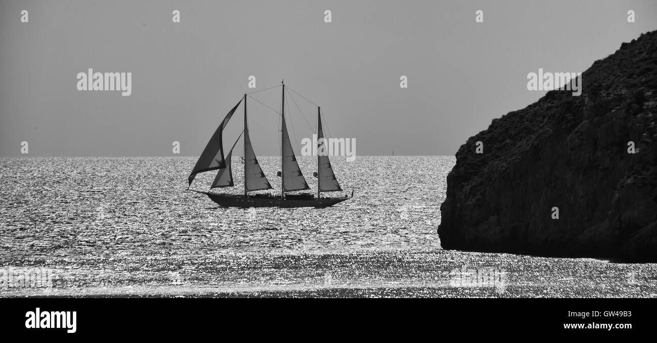 Three masted sailing boat in full sail on calm sea Stock Photo