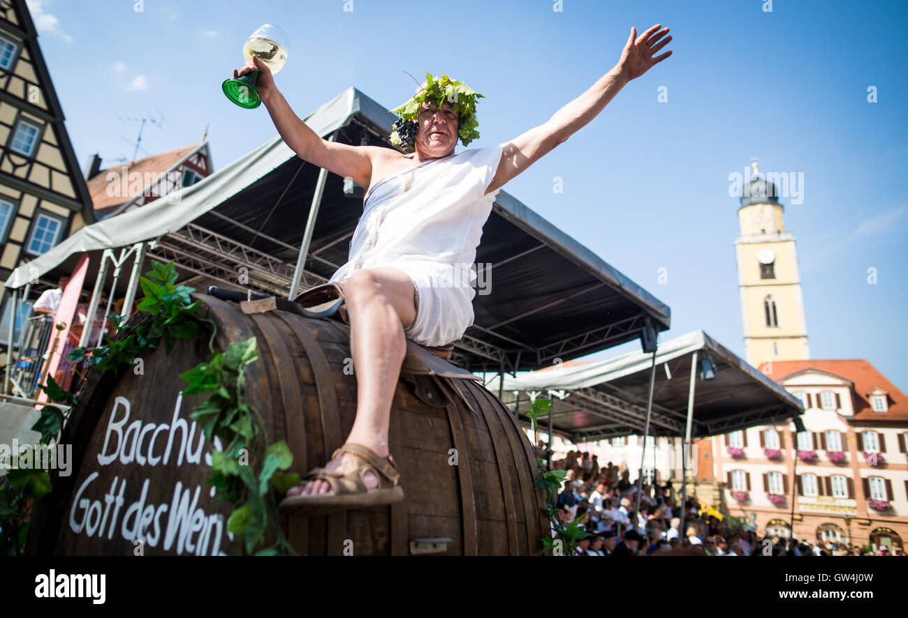 A participant of the state festival parade dressed as 'Bacchus - Gott des Weins' sitting on a barrel in Bad Mergentheim, Stock Photo