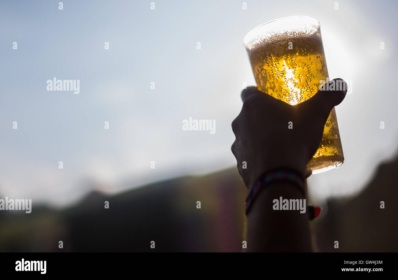 A visitor holding up a beer at the Lollapalooza festival in Berlin, Germany, 11 September 2016. PHOTO: SOPHIA KEMBOWSKI/dpa - Stock Image