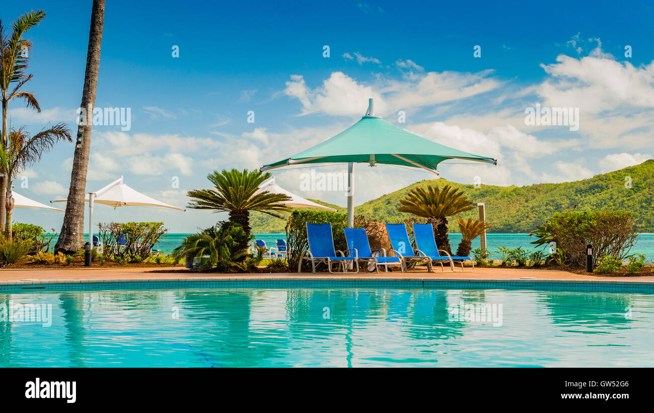 Deckchairs by the pool on Daydream Island, a remote island in the Whitsundays off the coast of Queensland - Stock Image