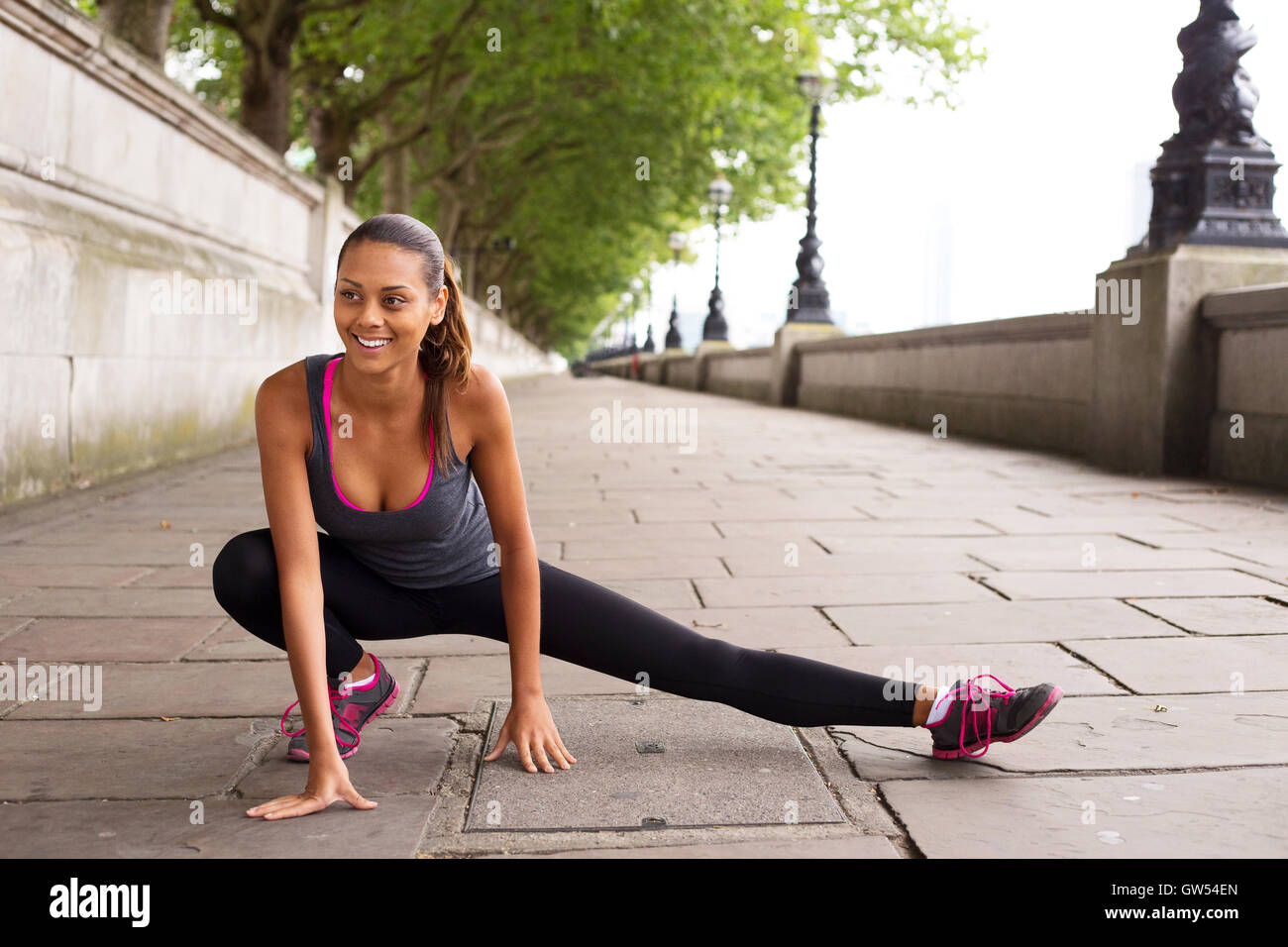 fitness woman stretching her leg muscles before going running - Stock Image