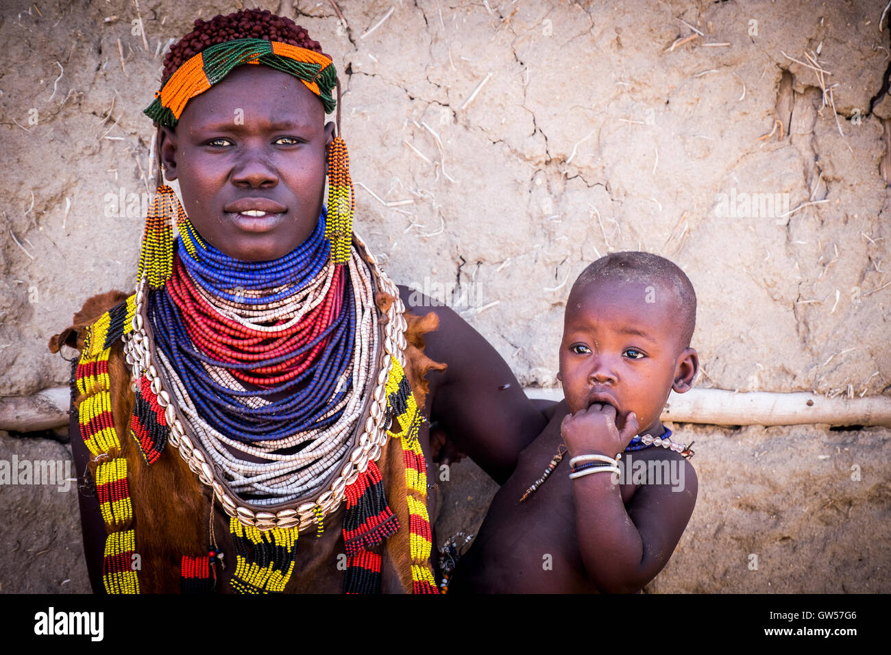 A woman and her child of the Karo tribe in the Omo Valley of Ethiopia.  She wears extensive beaded ornamentation. - Stock Image