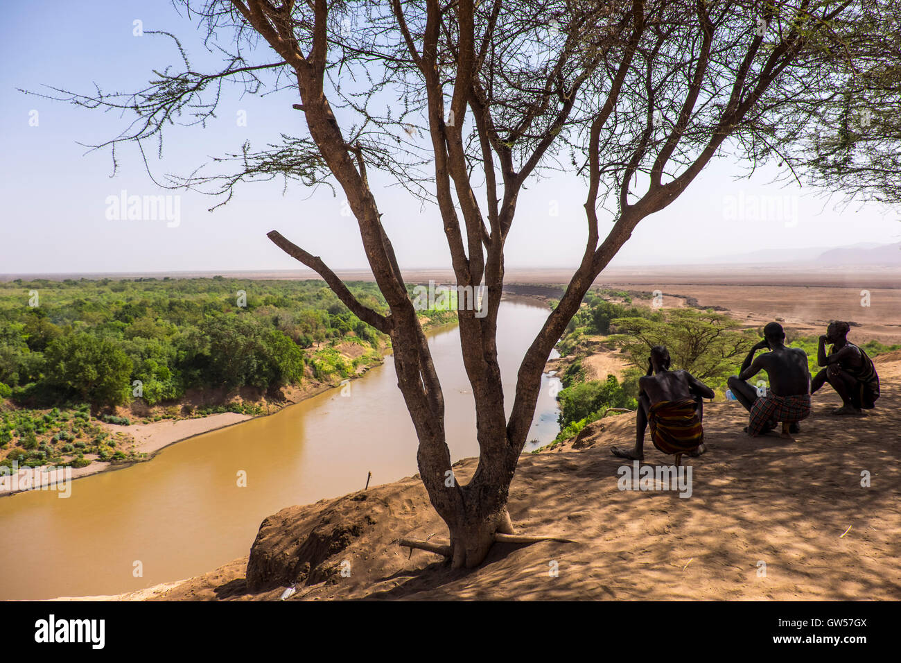 Three men of the Karo tribe sit under a tree in the shade looking down on the Omo River Valley in Ethiopia - Stock Image