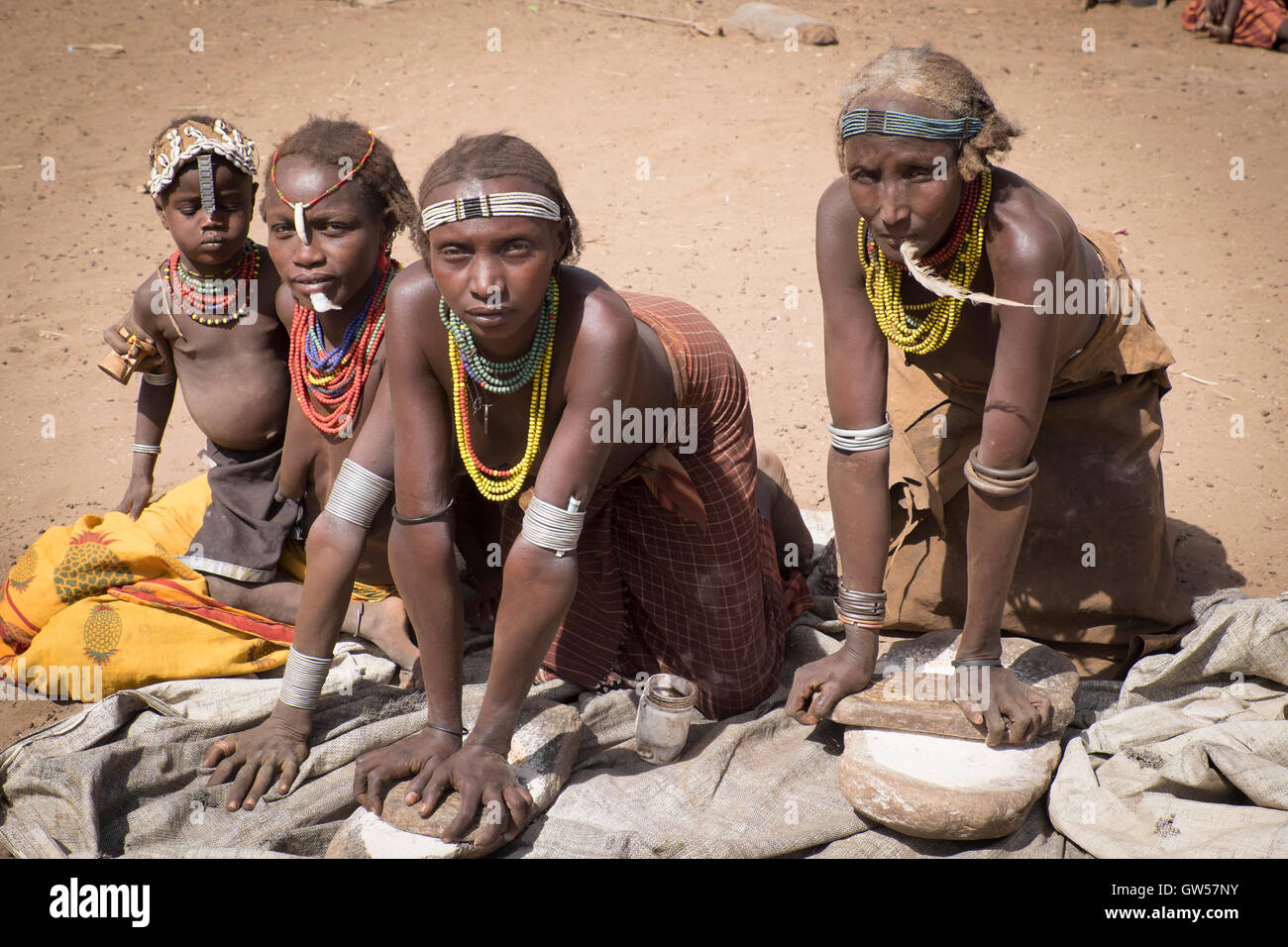 Four generations of the women of the Dasanech tribe in the Omo River Valley of southern Ethiopia grind sorghum for - Stock Image
