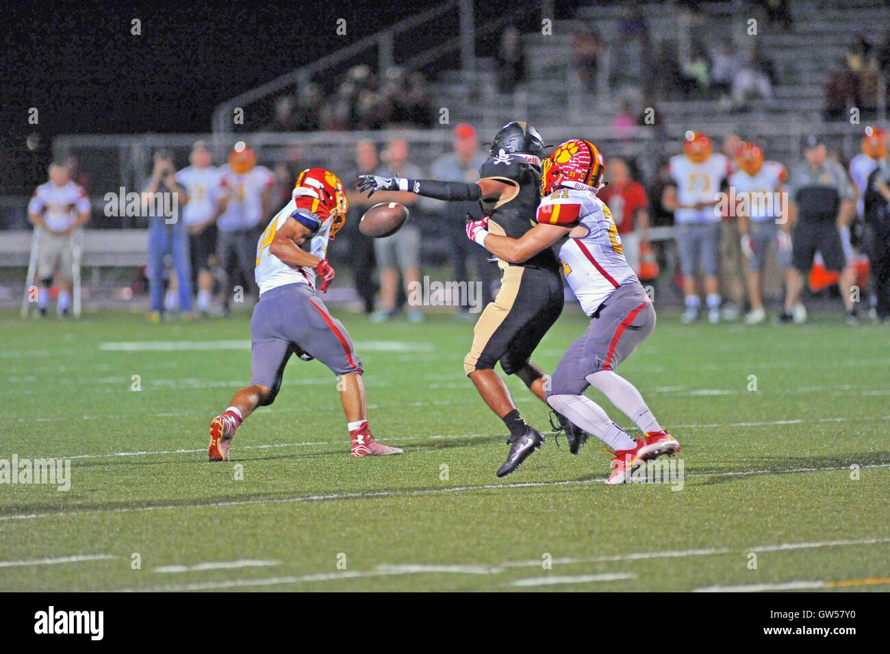 Pass receiver has a pass broken up in the midst of double coverage during a high school football game. USA. - Stock Image