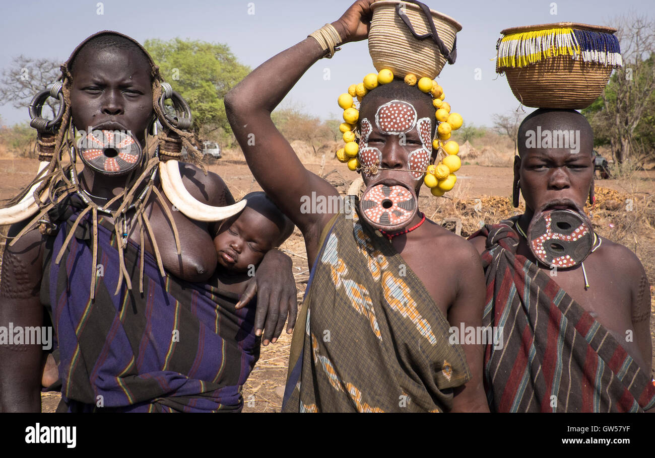 Three Mursi women of the Omo Valley in Ethiopia with lip plates, bone earring, headdresses and ritual body paint, - Stock Image