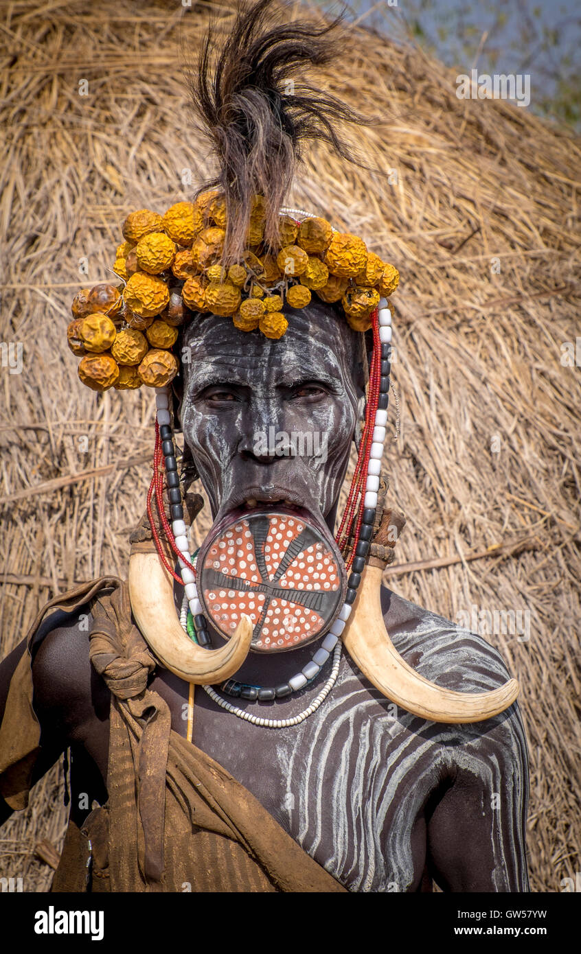 Mursi woman of the Omo Valley in Ethiopia with lip plate, body painting, headdress, feathers and bone earrings - Stock Image