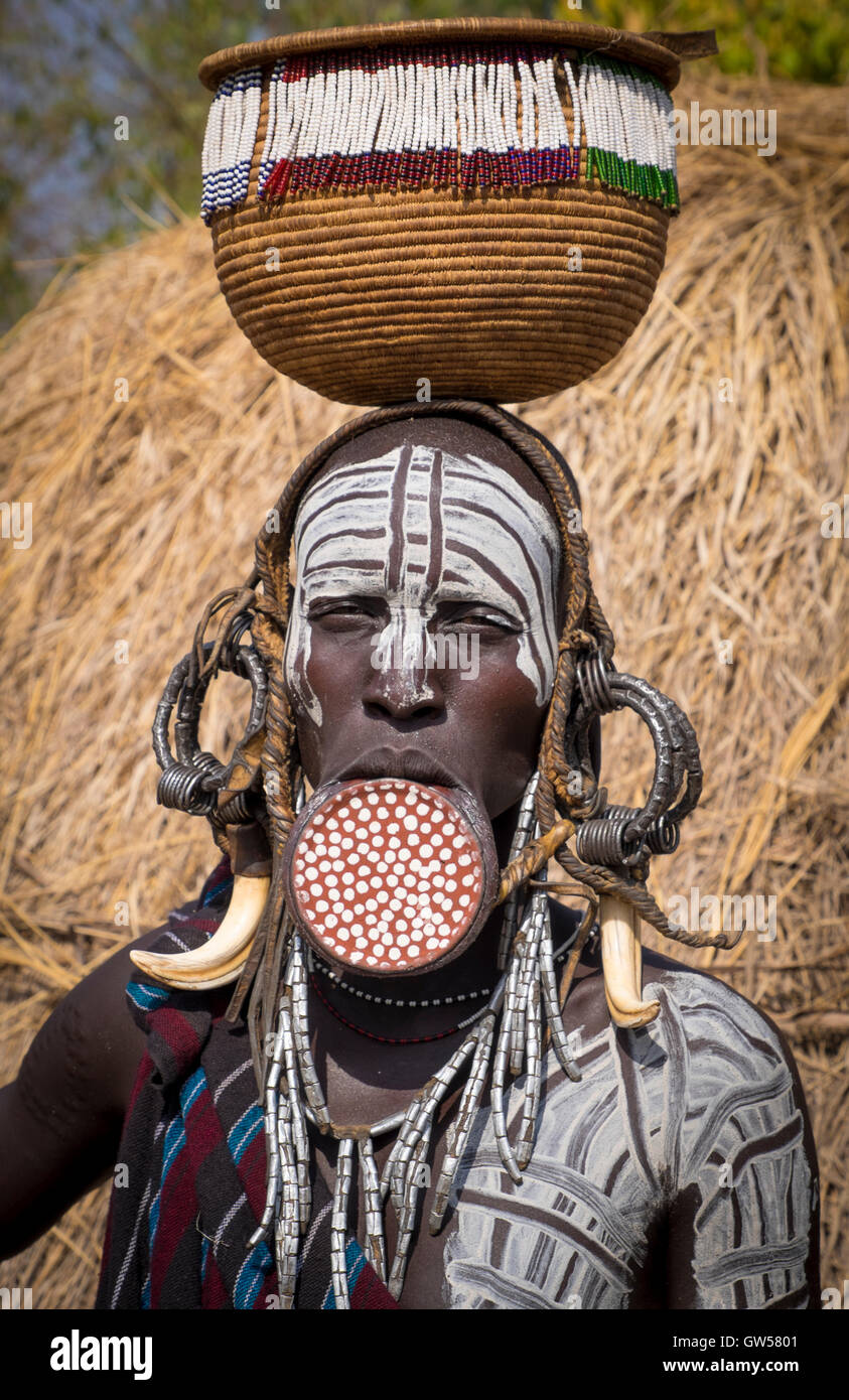 Mursi woman of the Omo Valley in Ethiopia with lip plate, body painting, bone earrings and basket - Stock Image
