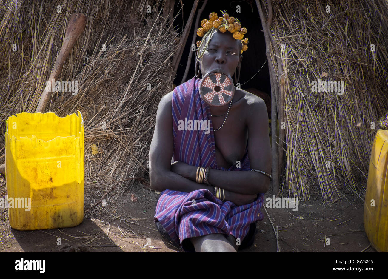Mursi woman of the Omo Valley in Ethiopia sits in front of her thatched hut with a mouth plate inserted in her lower - Stock Image