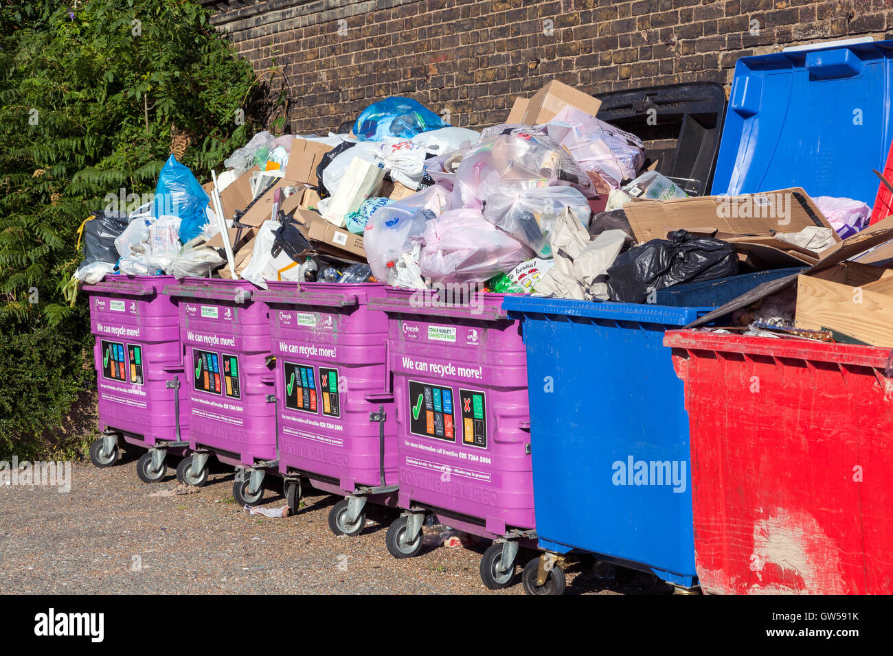 Overflowing mixed recycling bins in Limehouse, Tower Hamlets, London Stock Photo