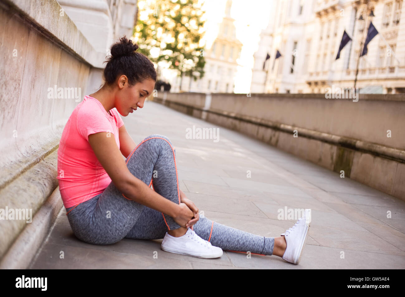 young woman feeling her painful ankle after exercise - Stock Image