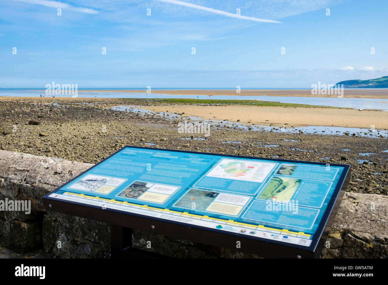 Bilingual information sign about GeoMon Global Geopark overlooking the sands in AONB at Red Wharf Bay Isle of Anglesey Stock Photo