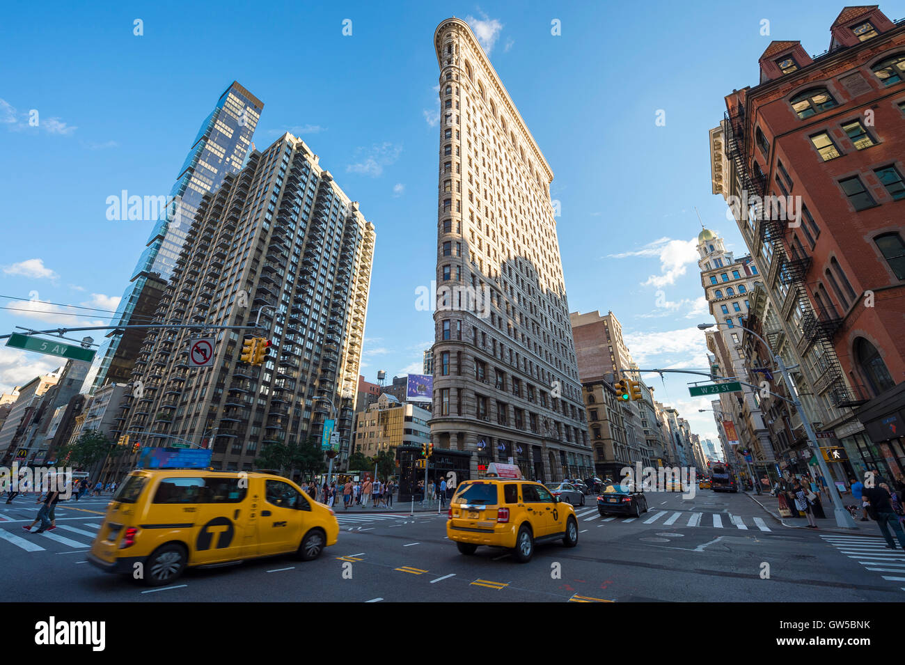NEW YORK CITY - SEPTEMBER 4, 2016: Yellow taxis head downtown on Broadway past the iconic Flatiron Building. - Stock Image