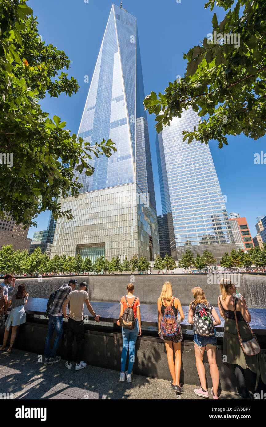NEW YORK CITY - SEPTEMBER 4, 2016: Visitors stand at the edge of the National September 11 Memorial in front of - Stock Image