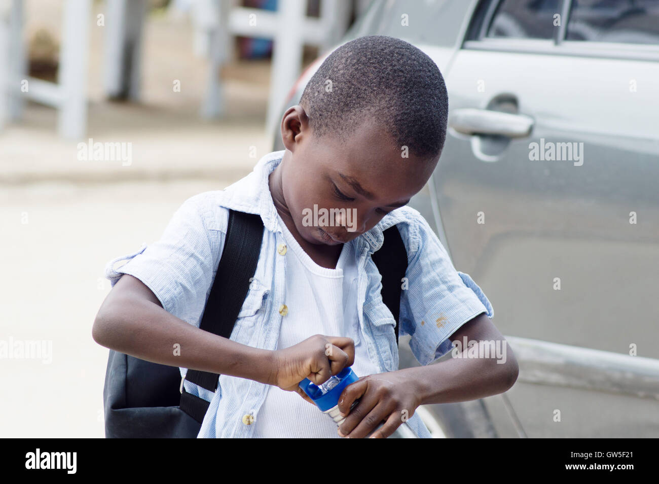 child opens his bottle containing water because he is thirsty Stock Photo