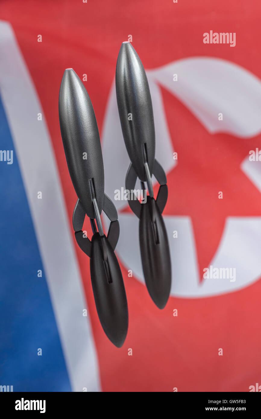 Toy rocket & North Korean flag as metaphor for tensions on Korean Peninsula, DPRK / NOKO nuclear tests & - Stock Image