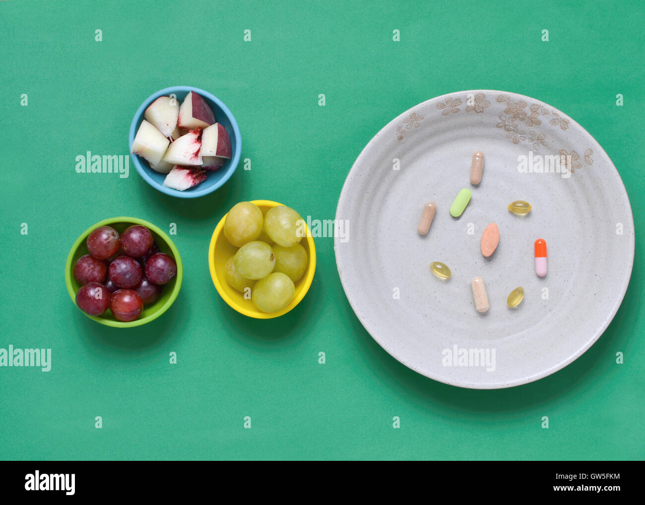 Dietary supplements, and fruits in colorful bowls, on greet tablecloth Stock Photo