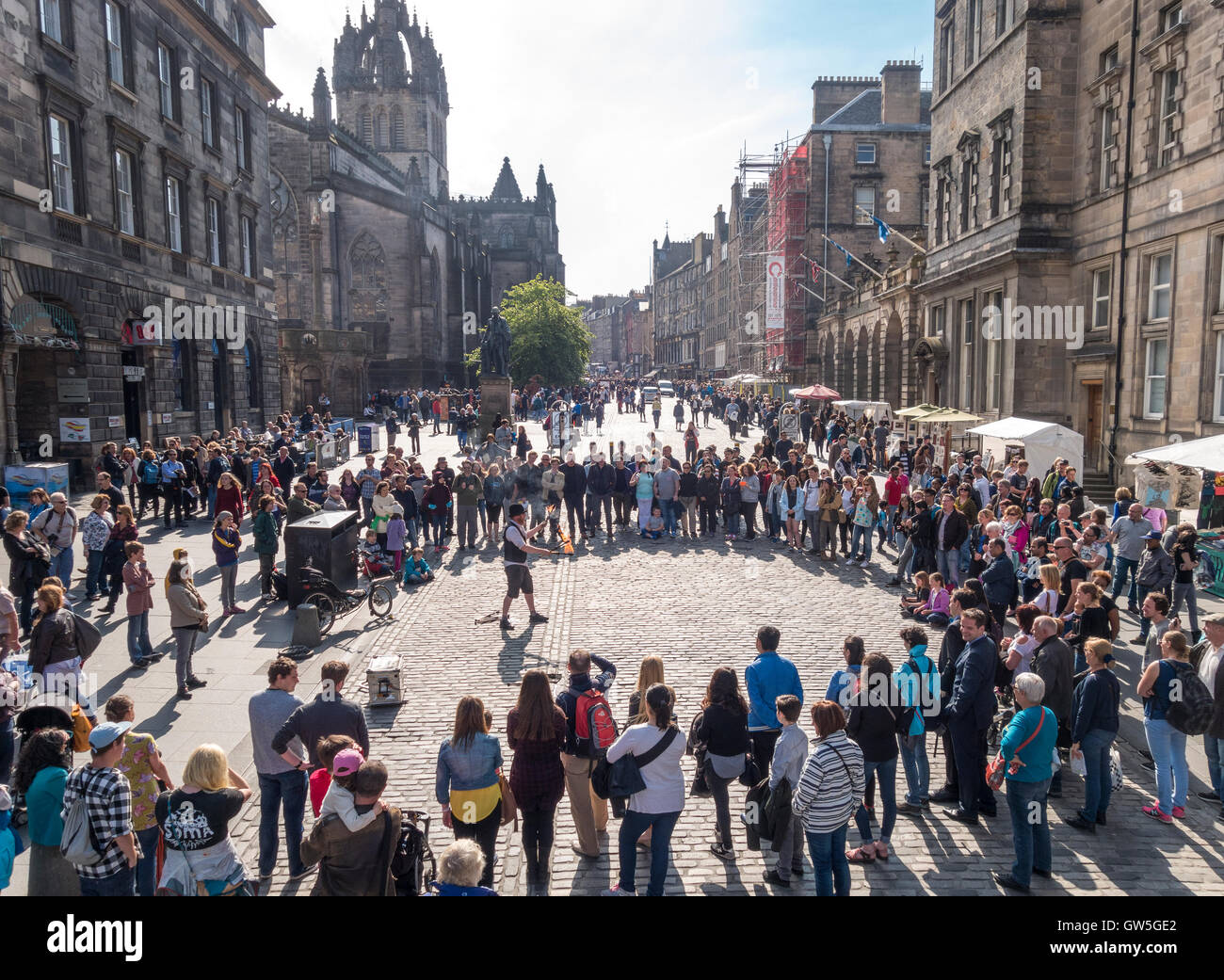 Edinburgh Royal Mile. Edinburgh High Street with fire performer and a circle of visitors, tourists looking on. - Stock Image