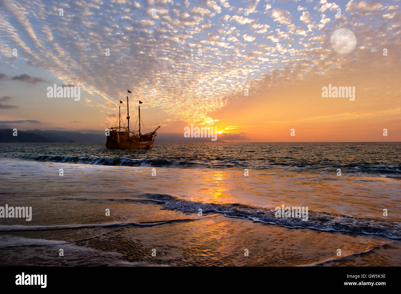 Pirate ship fantasy is an old wooden pirate ship with full flags as the sun sets on the ocean horizon in a colorful Stock Photo