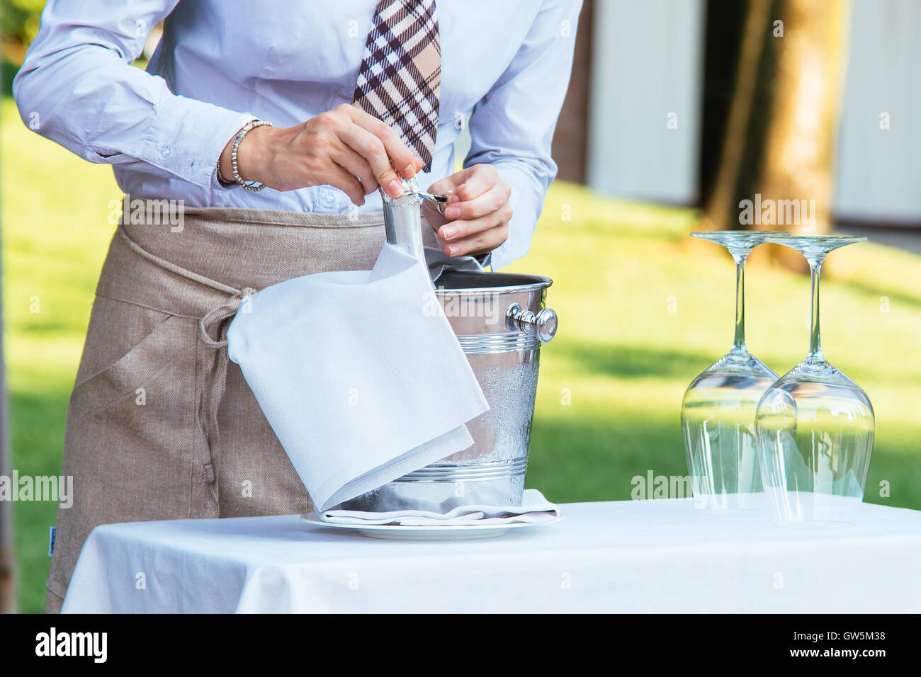 Waiter opening a champagne bottle for a toast - Stock Image