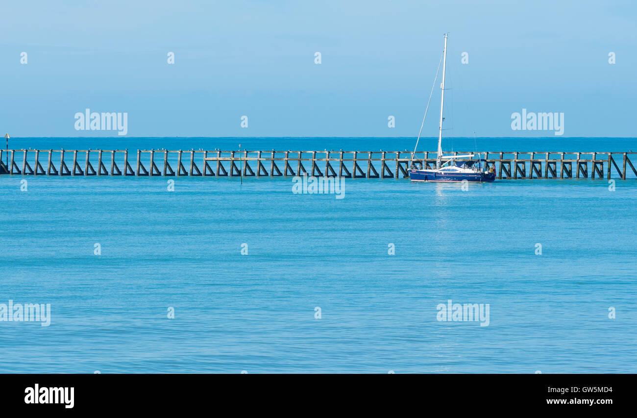 Calm sea. Yacht exiting a river estuary on a calm flat blue sea. - Stock Image