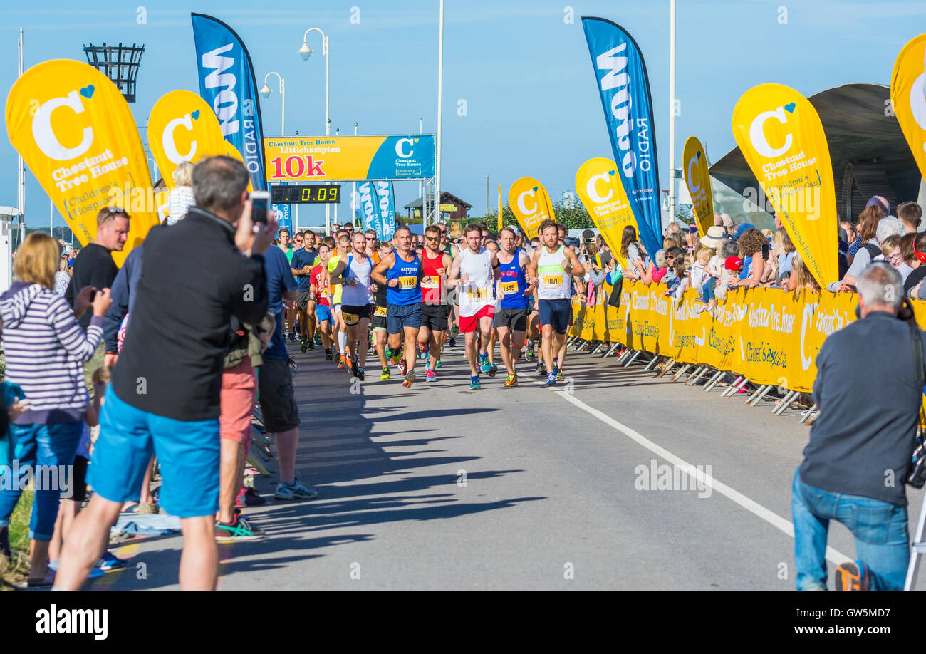Start of a charity run showing runners and photographers. - Stock Image
