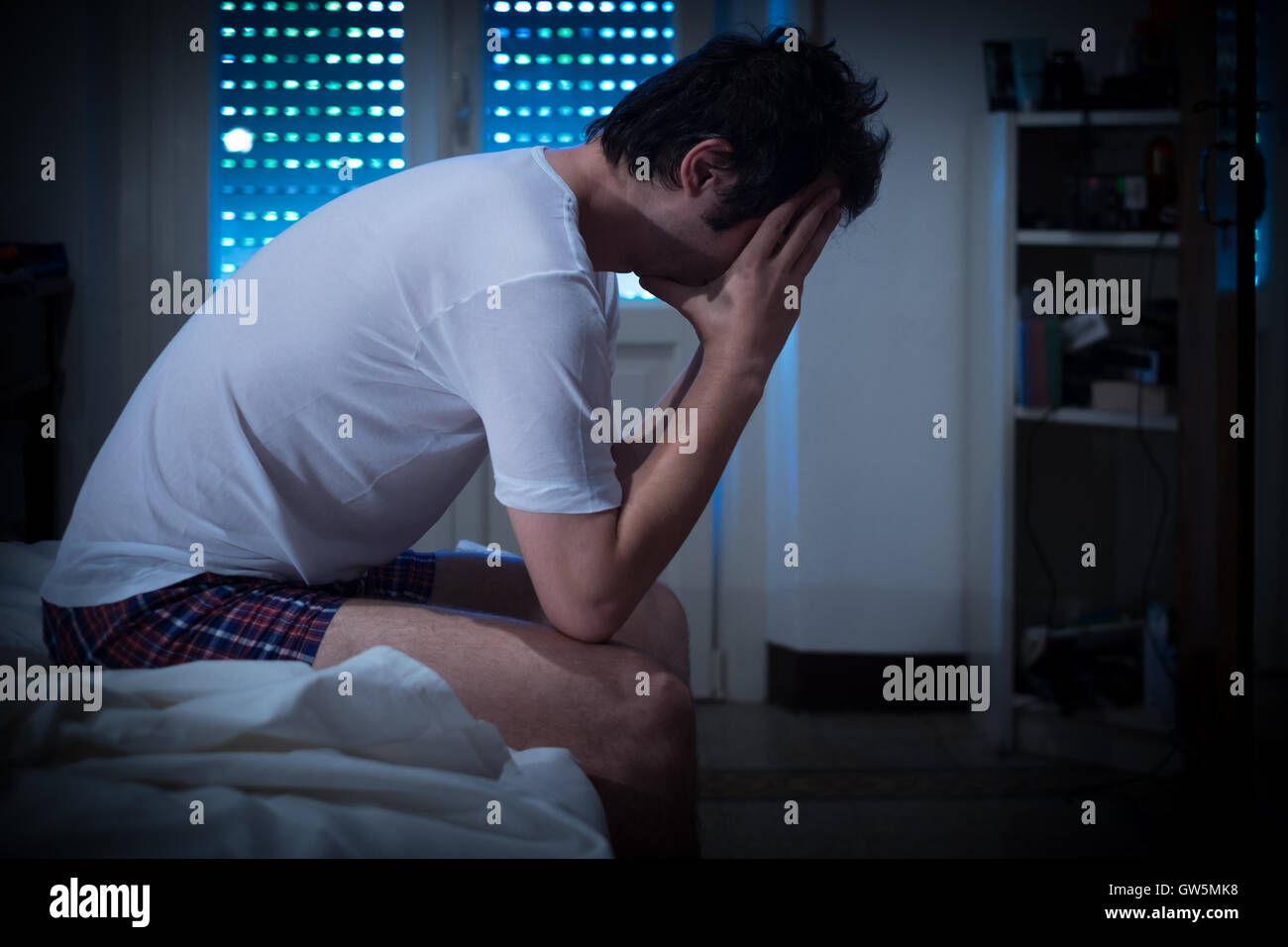 Sad and lonely man seated on his bed - Stock Image