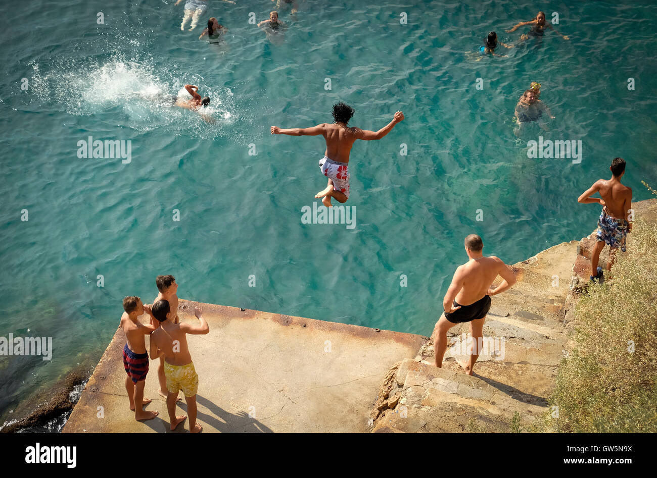 Young boys dive off a platform into the blue waters of the Mediterranean Sea while swimmers watch below - Stock Image