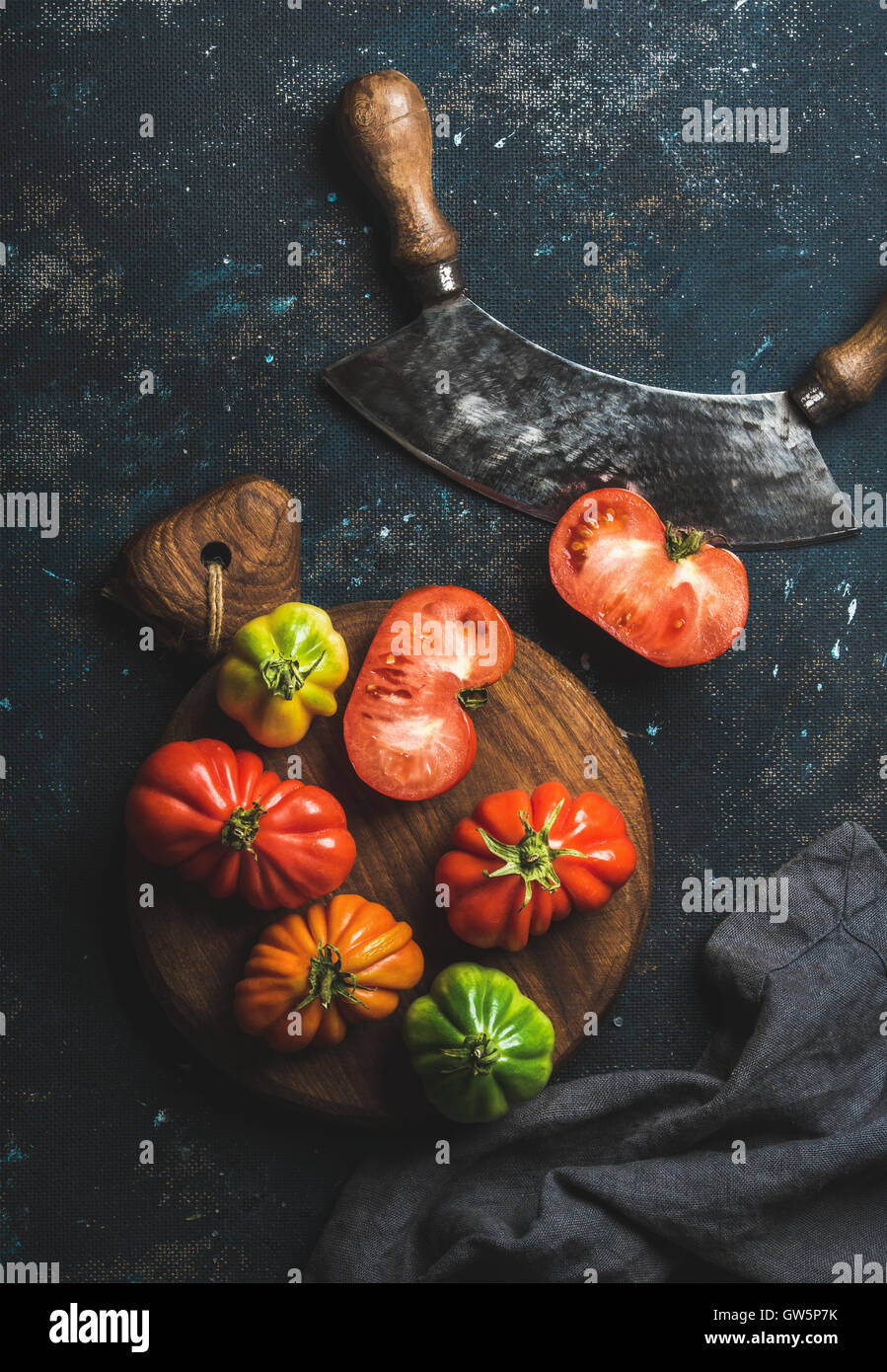 Fresh colorful ripe heirloom tomatoes on wooden board - Stock Image