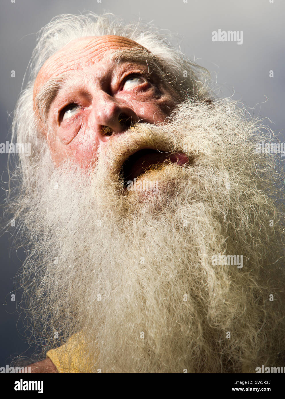 Old man with white beard open mouthed looking skywards. - Stock Image