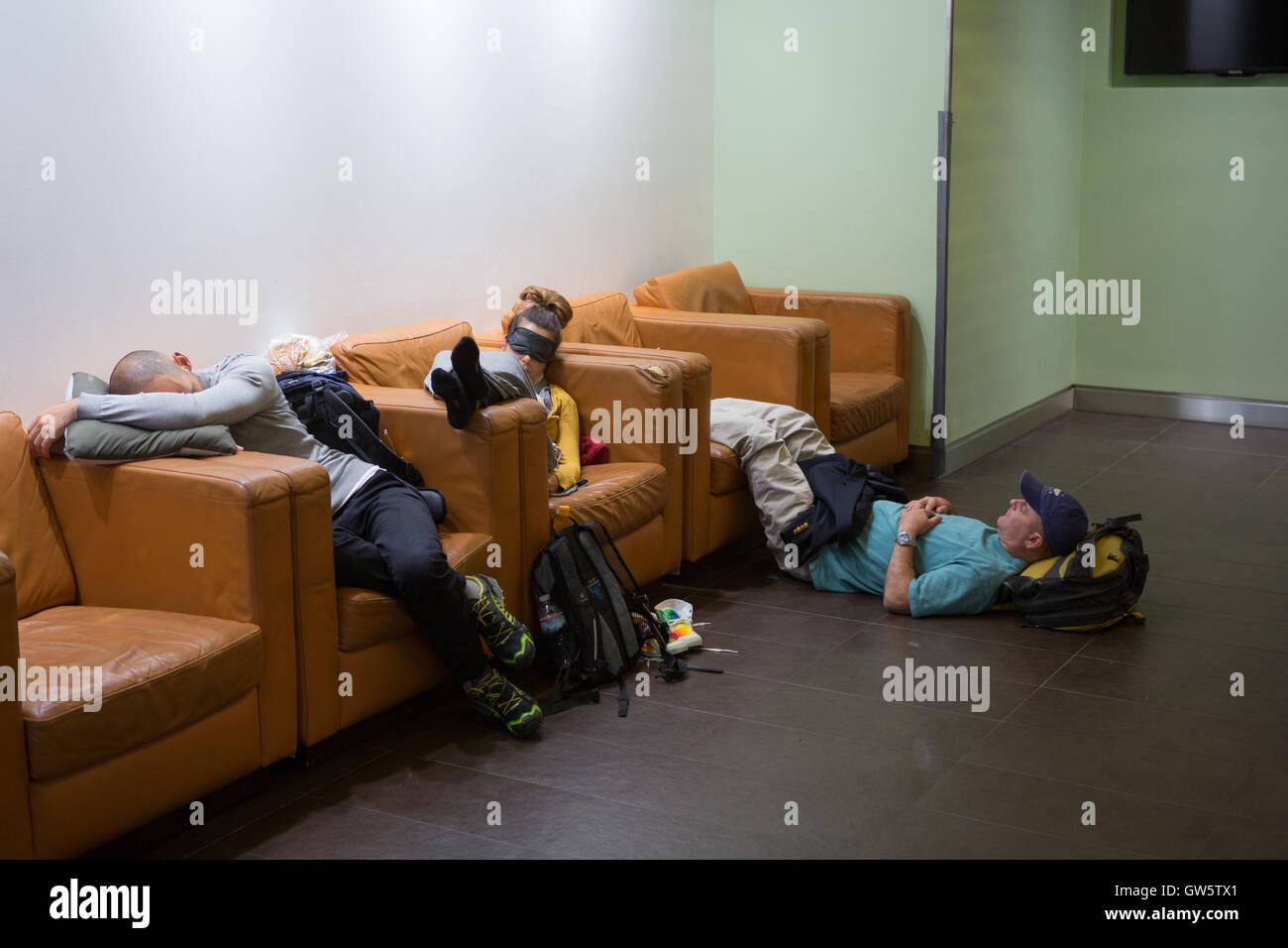 Three passengers in an airport departure lounge sleep whilst waiting for a delayed flight - Stock Image