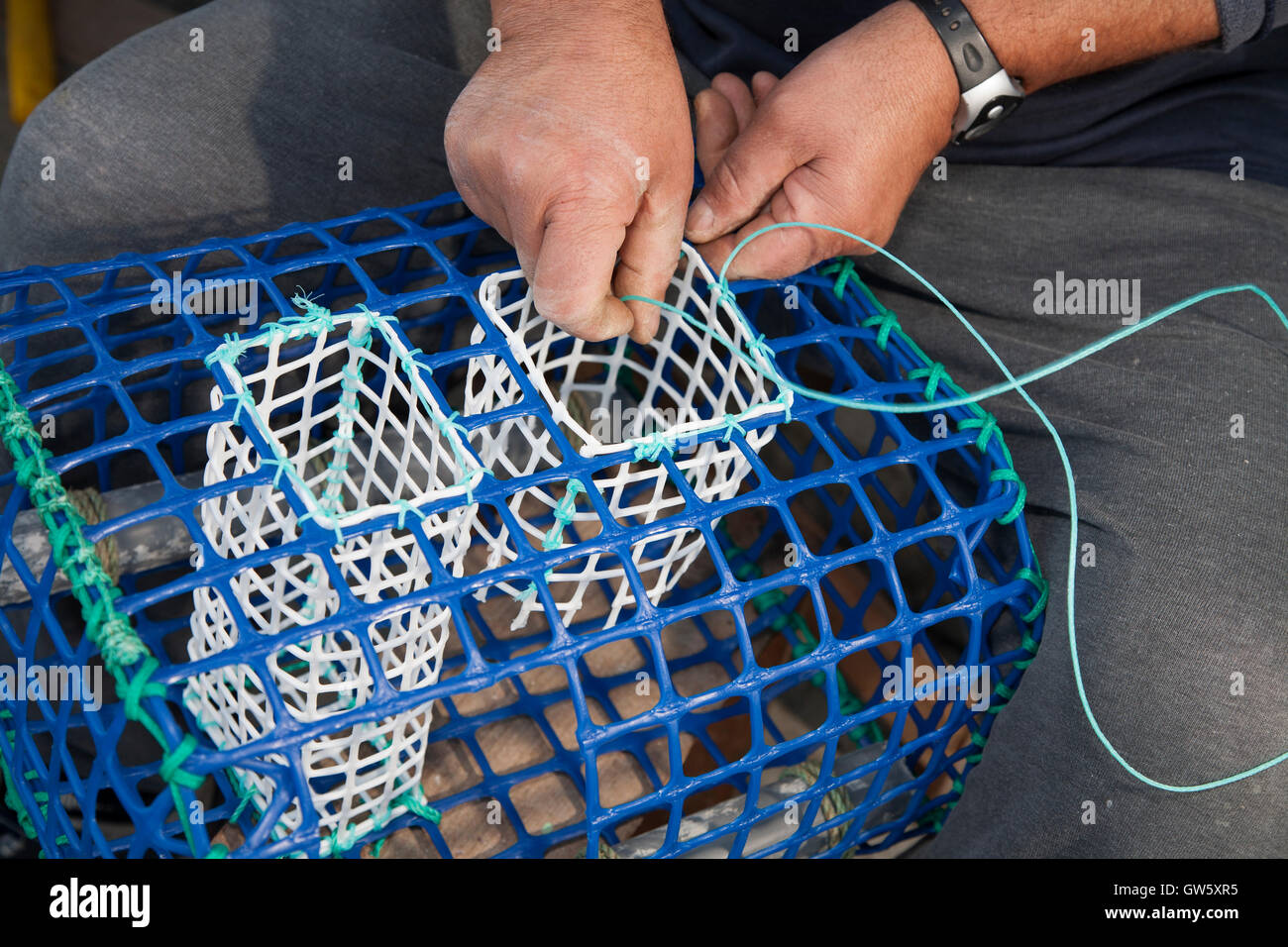 Fisherman making traps for octopus and crustaceans. Sesimbra, Portugal - Stock Image
