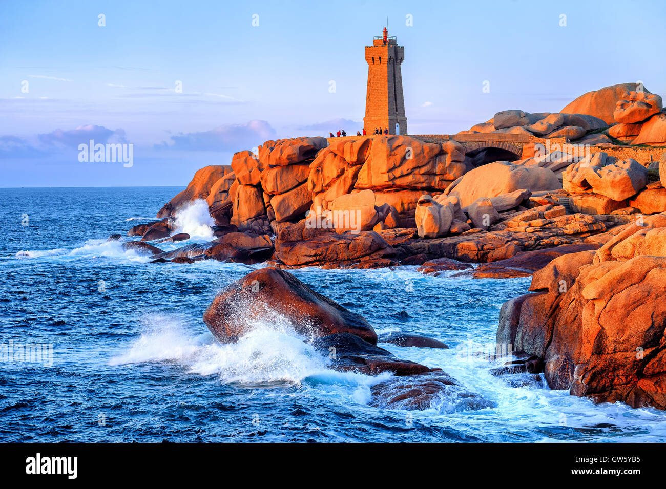 Lighthouse of Ploumanach Mean Ruz in Perros-Guirec on Pink Granite Coast, Brittany, France, on sunset Stock Photo