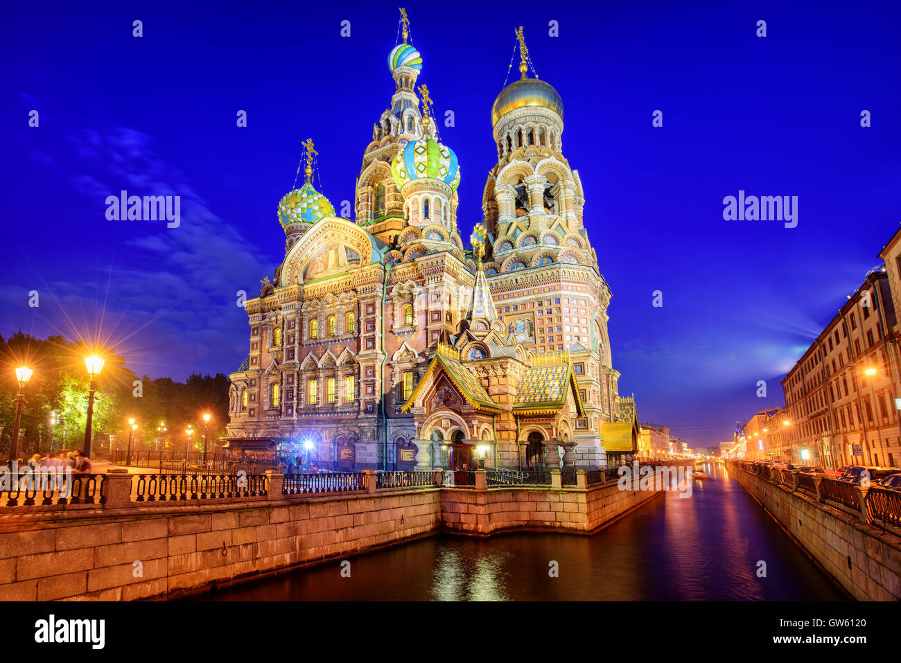 The orthodox Church of the Savior decorated with colorful onion domes on Griboyedov Canal illuminated at evening, - Stock Image