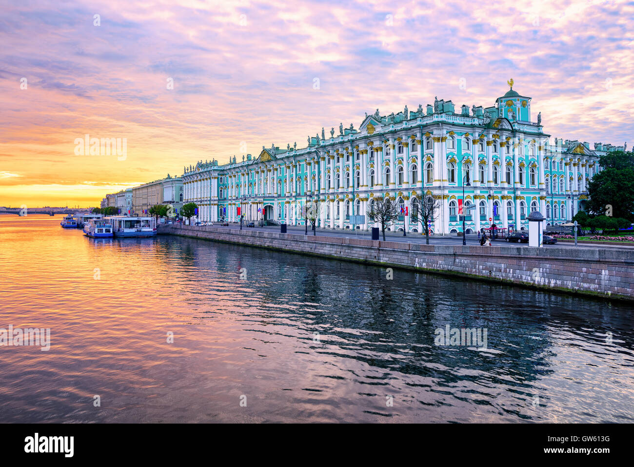 Winter Palace building housing Hermitage museum reflects in Neva river on dramatic sunrise, St Petersburg, Russia - Stock Image