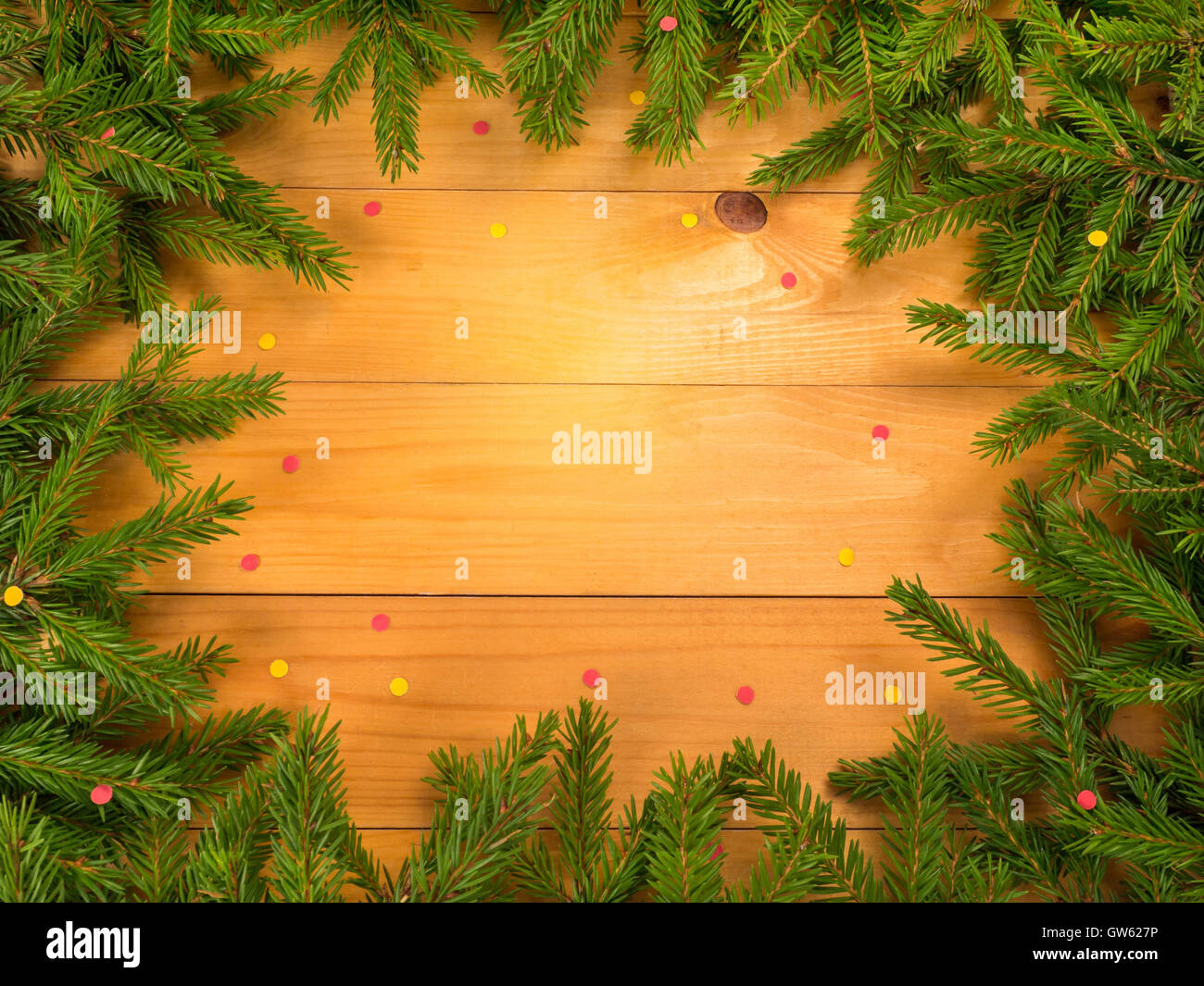 Christmas tree branches frame on the wooden planks background sprinkled with red and yellow confetti - Stock Image