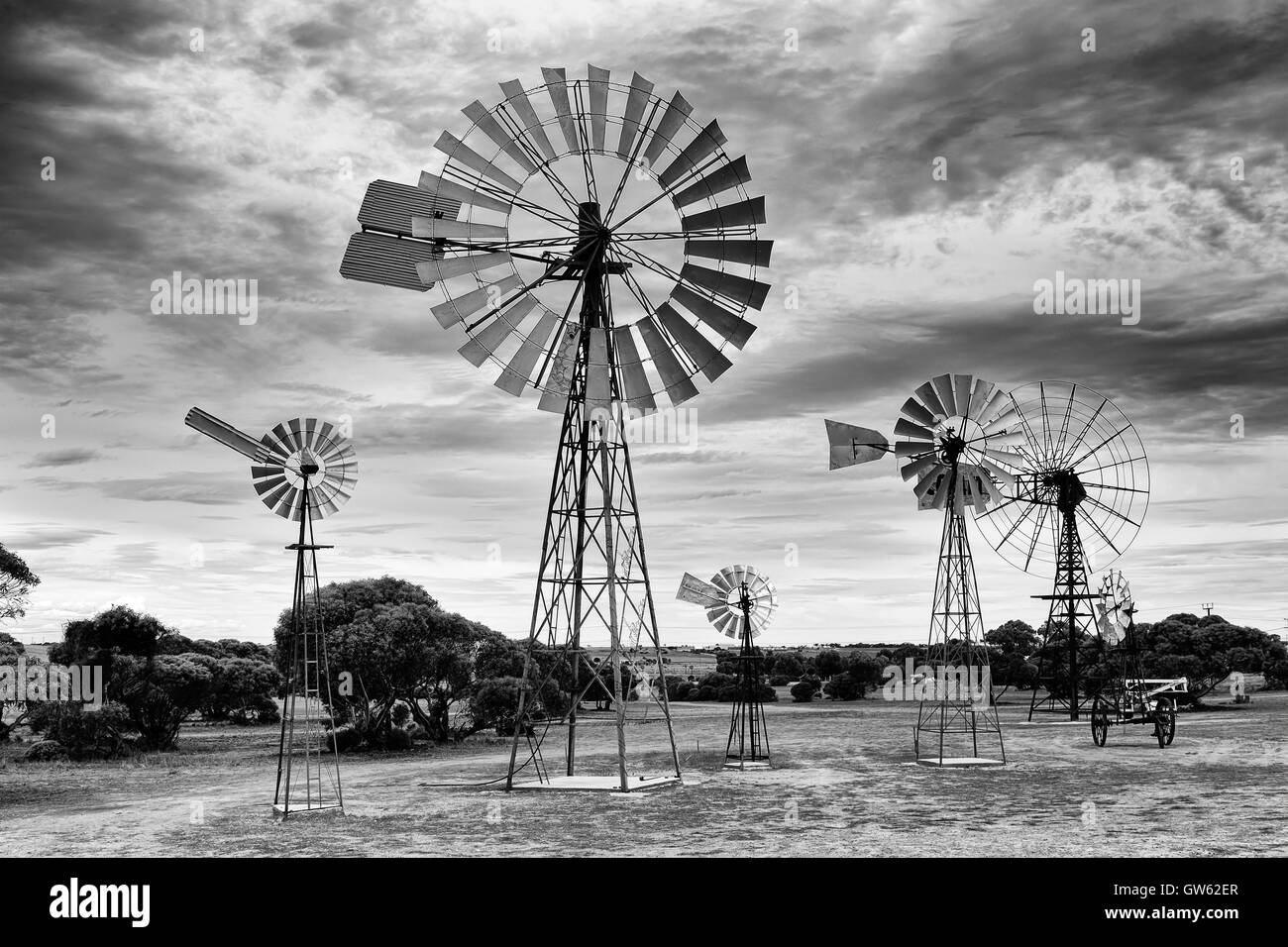 Array of historic traditional windmills in rural South Australia against cloudy sky on a hot summer day in black - Stock Image
