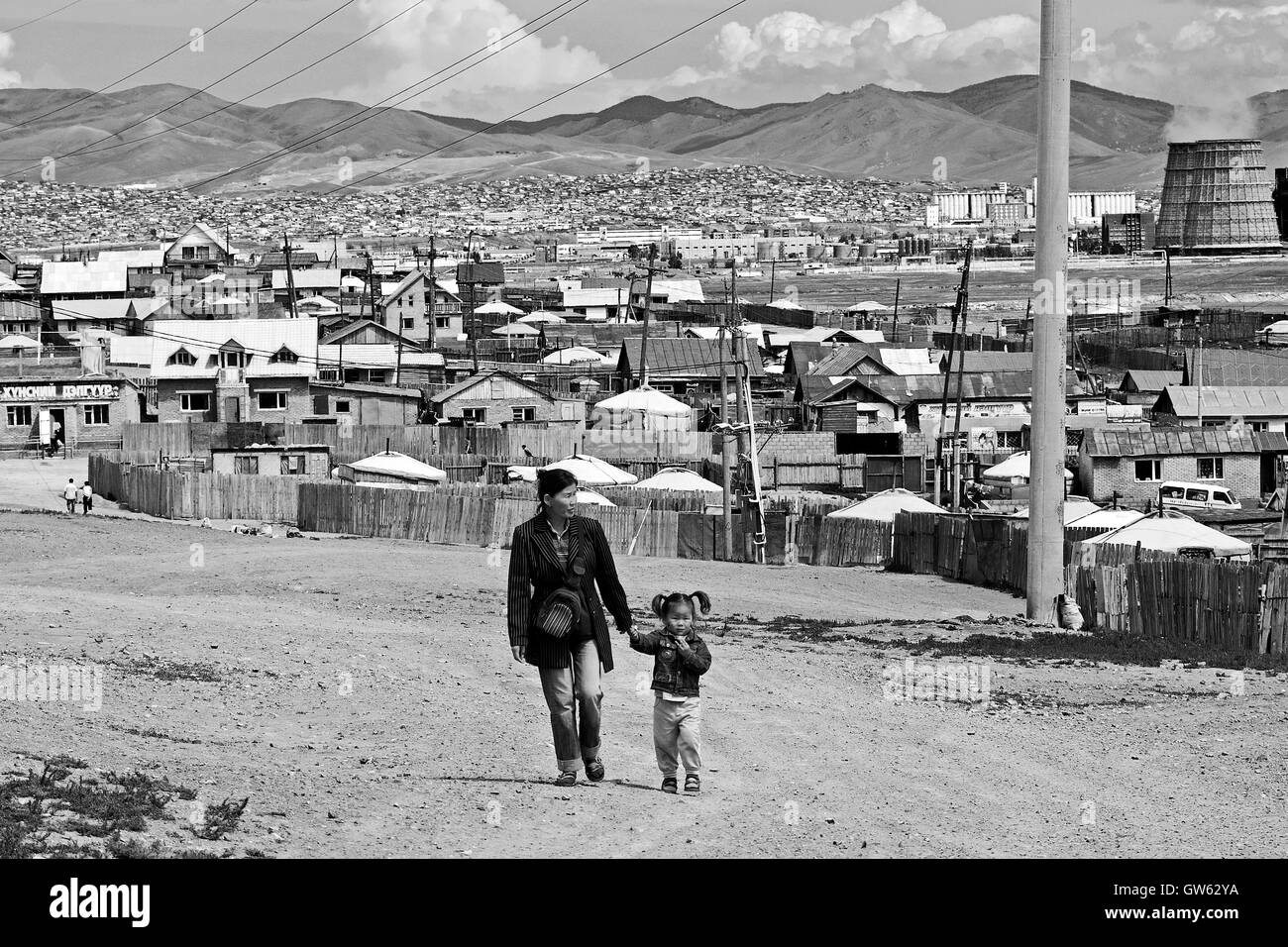 Mother and daughter walk along a road of the suburbs of Ulan Bator, Mongolia - Stock Image