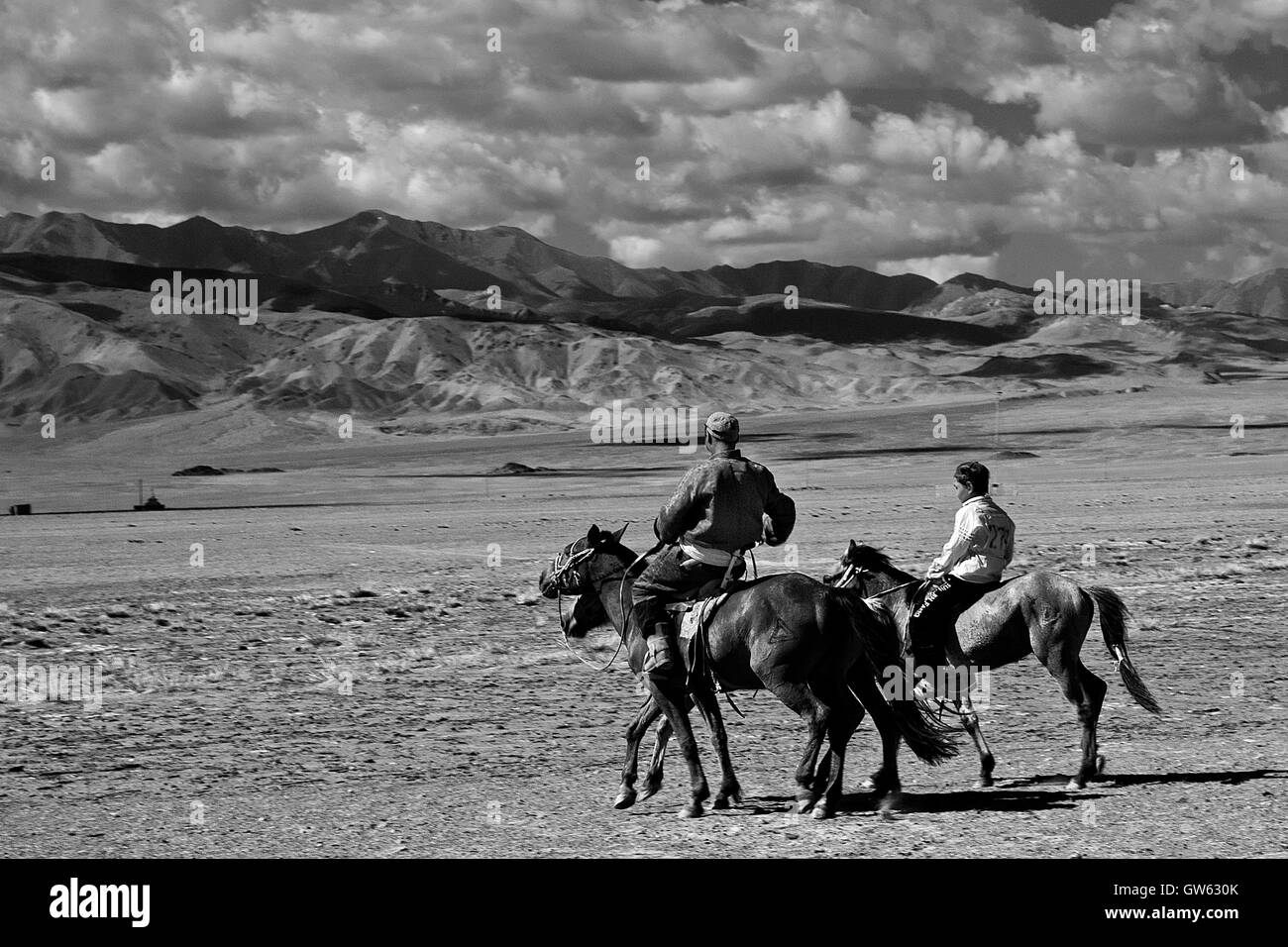 Father and son on horseback return home, after the horse race, part of the Naddam Festival, in the region of the - Stock Image