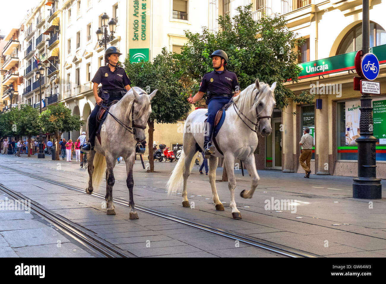 Spanish Mounted police officers on horses patrolling city of Seville, Andalusia, Spain. - Stock Image