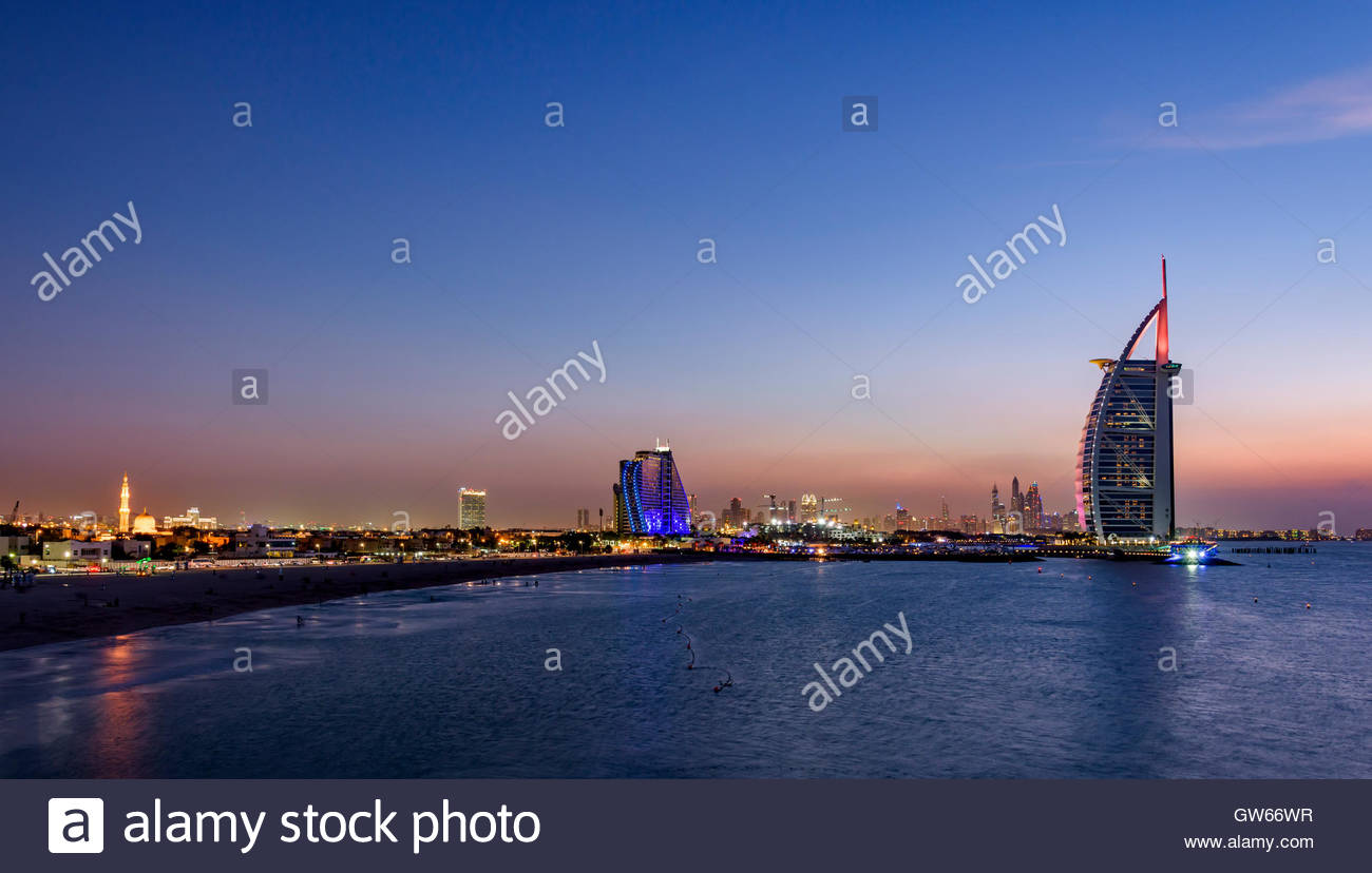 Sunset in Jumeirah, with on the left the Jumeirah Hotel, the Burj Al Arab and in the background the Marina of Dubai - Stock Image