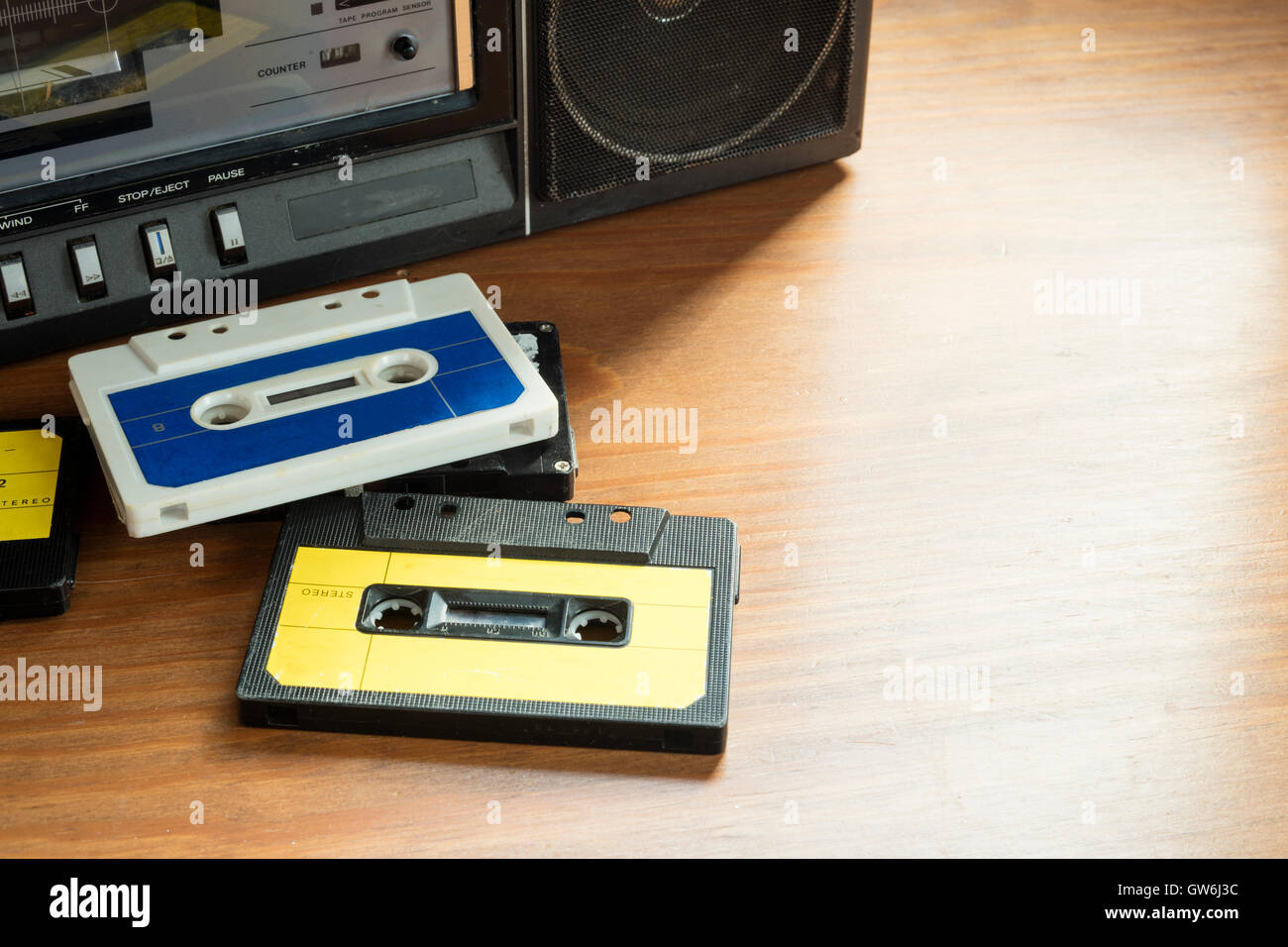 Vintage cassette tapes with radio-cassette player on a wooden table. - Stock Image