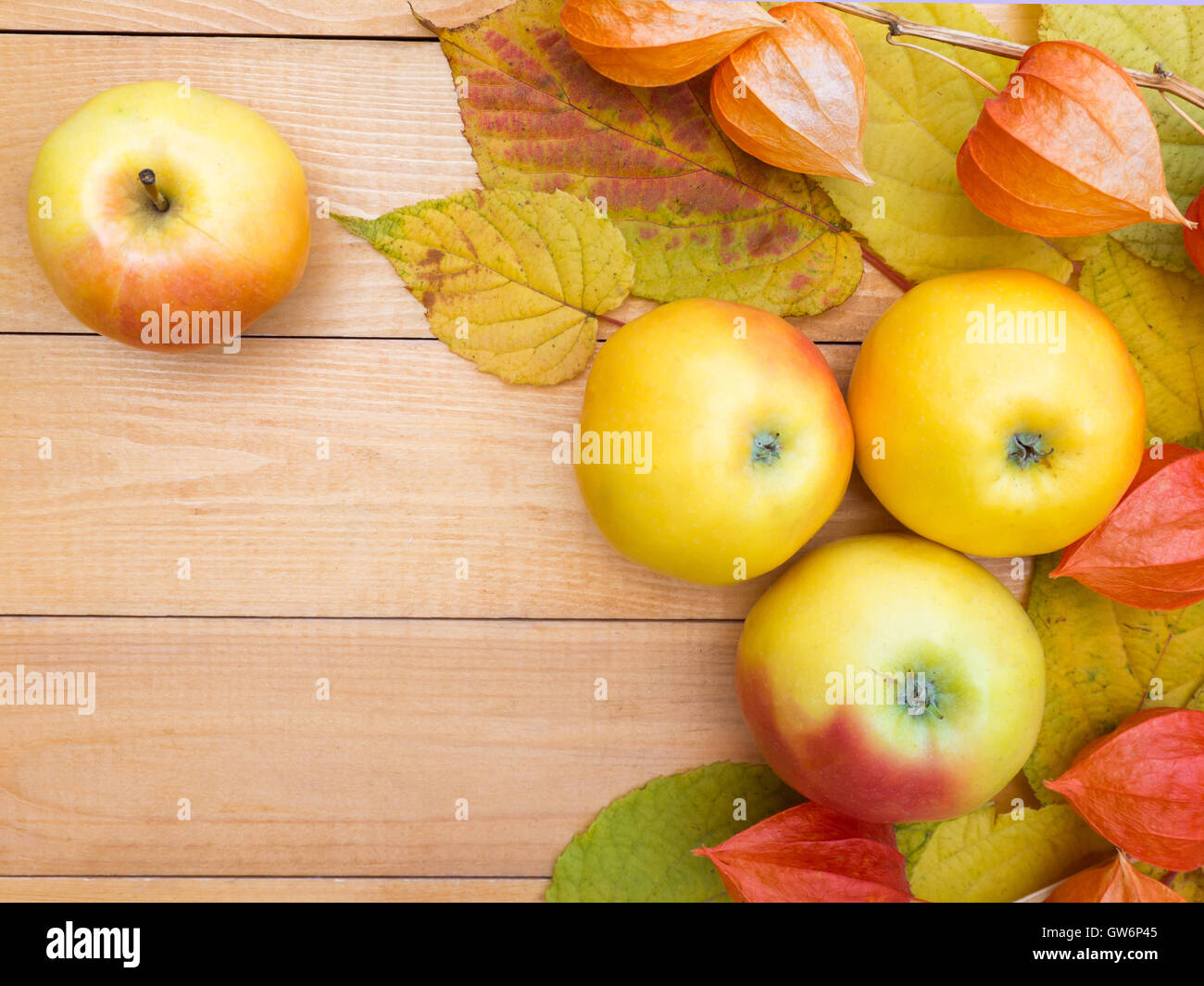 Apples, physalis lanterns and autumn leaves on the wooden planks background - Stock Image