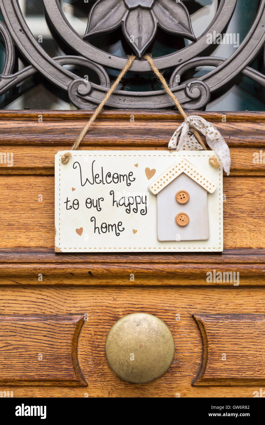Closeup of a small shield attached to a wooden door reading: Welcome to our happy home. - Stock Image