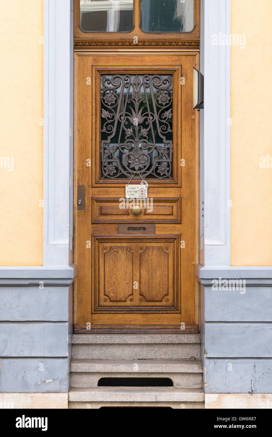 View on a wooden door with a small shield reading welcome to our happy home. - Stock Image
