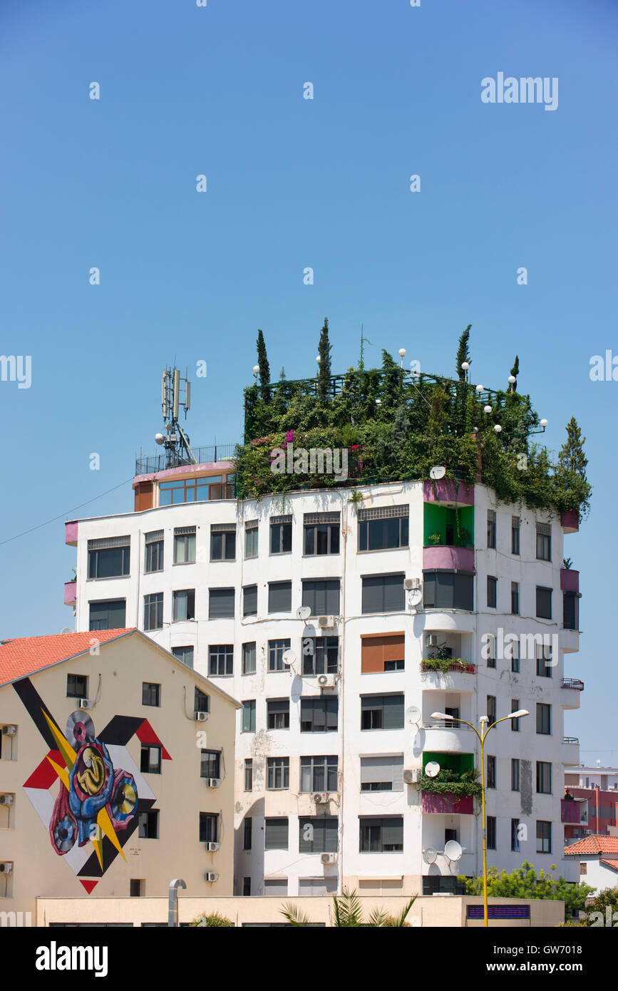 Colourful art on one building and a rooftop garden on another in central Tirana. - Stock Image